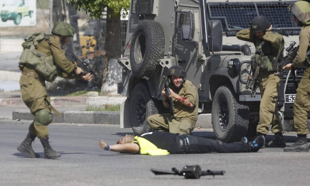 Após balear o agressor, tropa cerca o palestino que morreu em seguida Foto: Nasser Shiyoukhi / AP