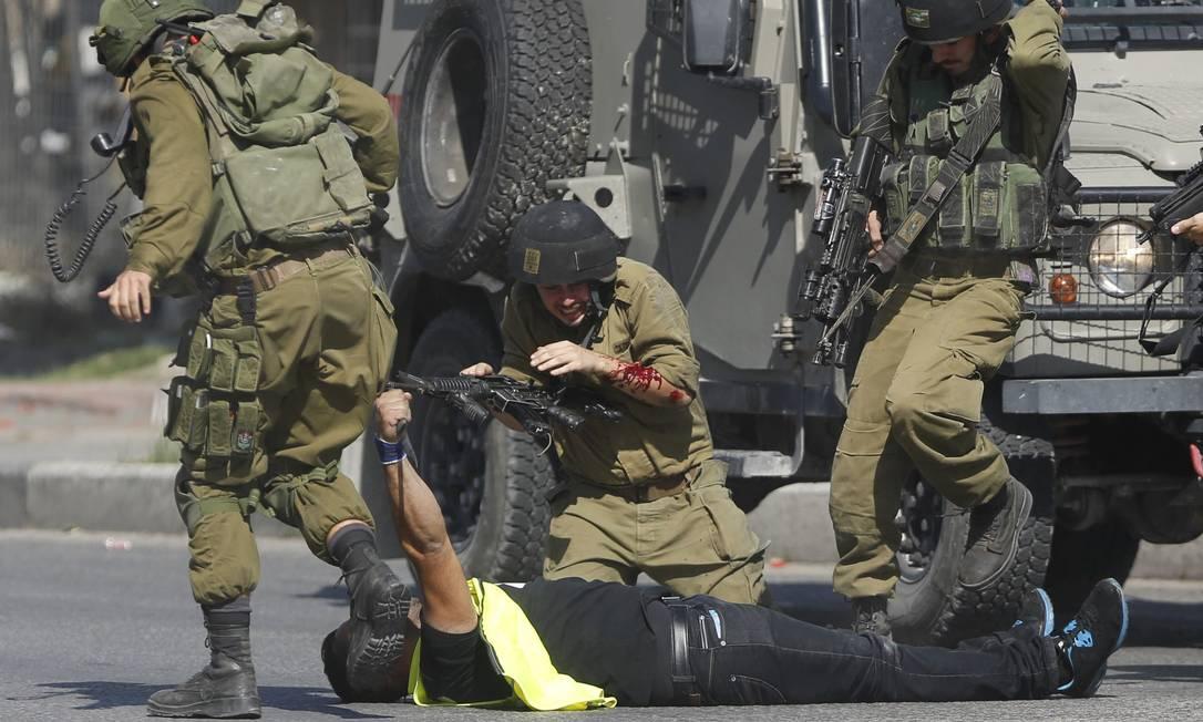 Mais soldados chegam para impedir que o palestino disfarçado ataque um dos militares Foto: Nasser Shiyoukhi / AP