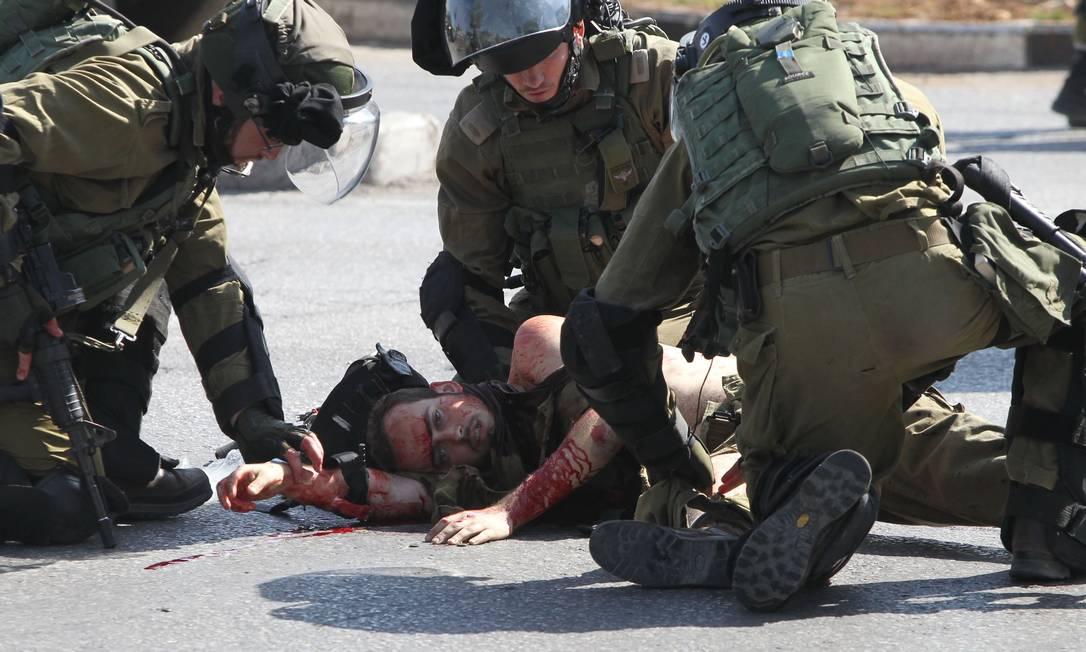 Muito ferido, o soldado recebe assistência de seus companheiros depois do ataque na entrada de Hebron Foto: HAZEM BADER / AFP