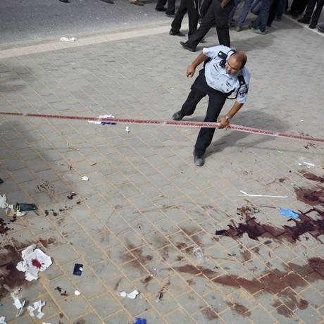 Policial observa local do ataque onde um israelense foi esfaqueado em Beit Shemesh. Um dos agressores morreu e outro foi ferido Foto: Oded Balilty / AP