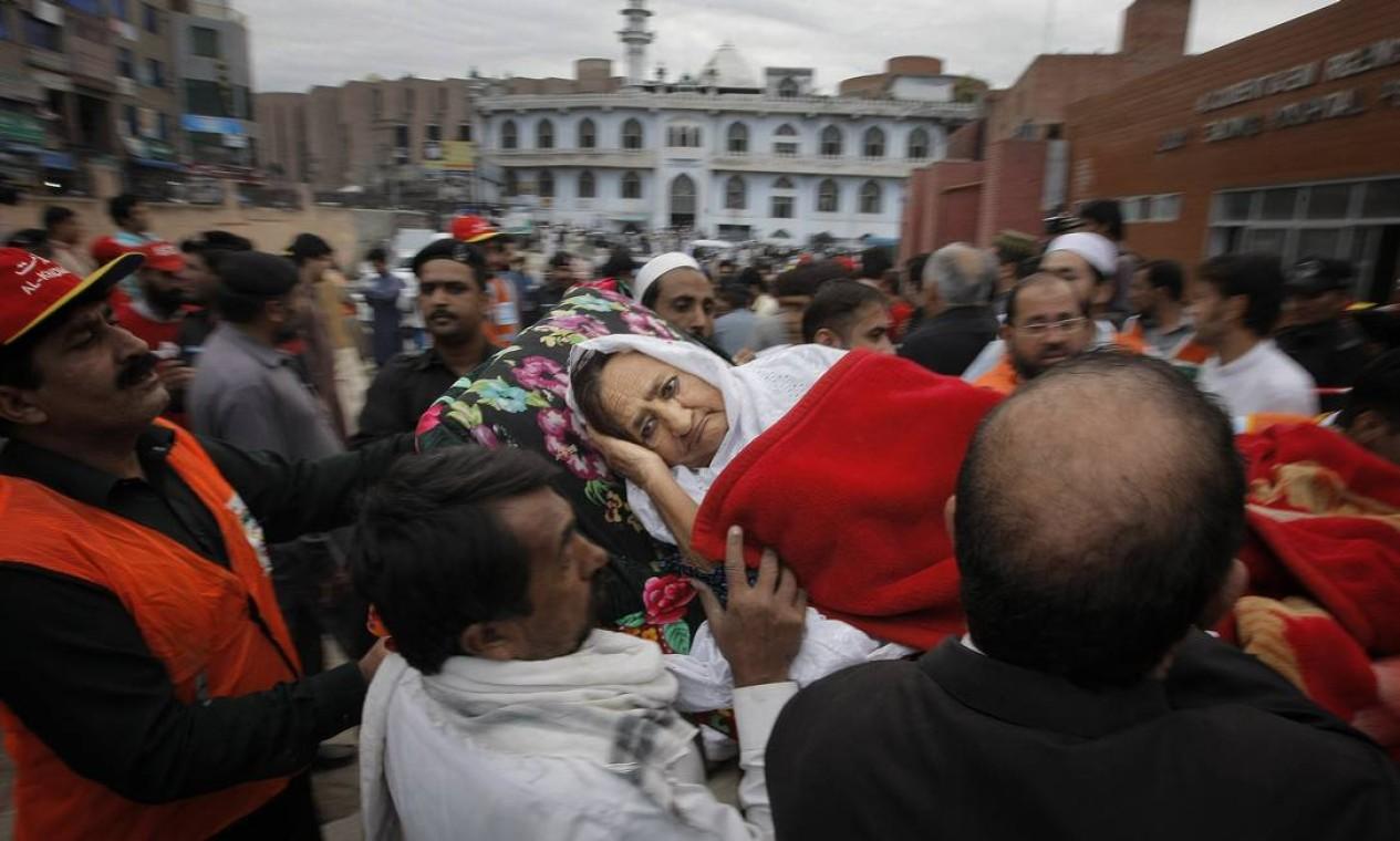 Pessoas se juntam para ajudar a socorrer uma senhora e levá-la ao hospital de Pershawar, no Paquistão. Na capital do país, as paredes se moviam e as pessoas deixavam os prédios em pânico, recitando versos do Alcorão Foto: Mohammad Sajjad / AP