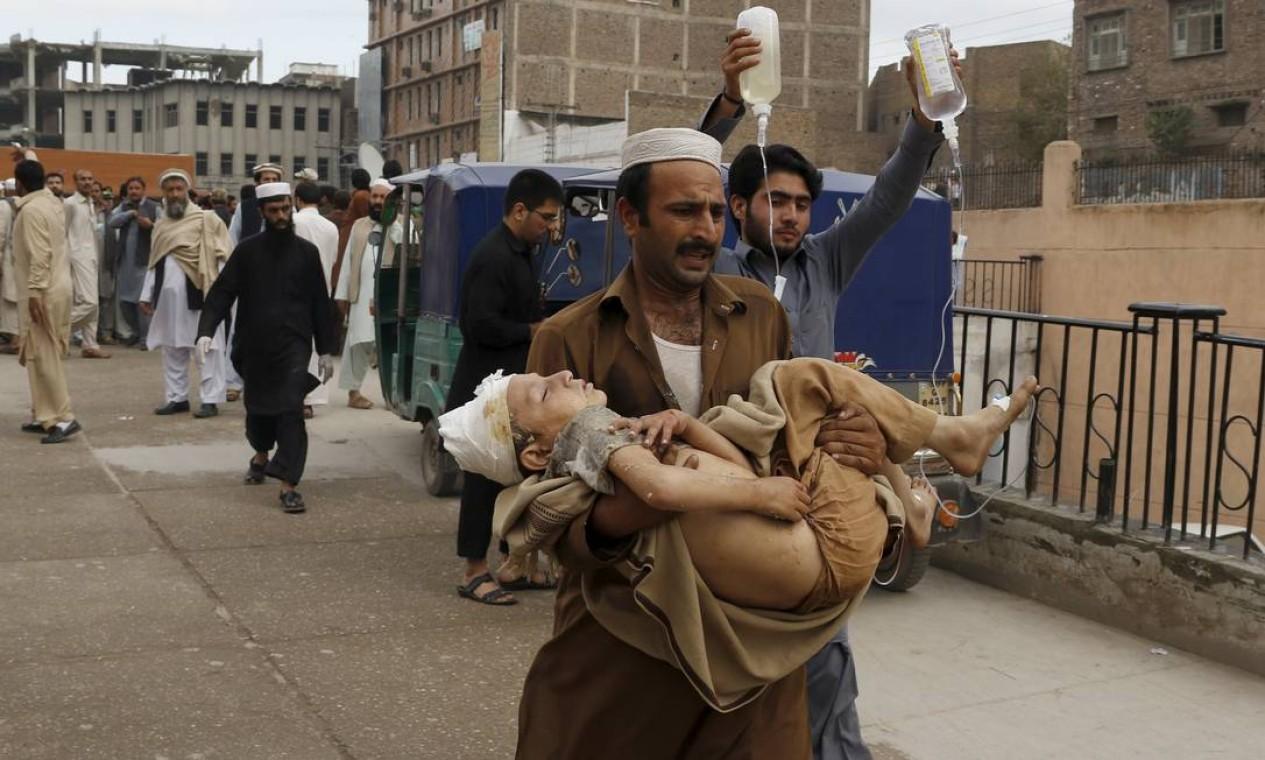 Homem carrega menino ferido pelo terremoto em Peshawar, no Paquistão. O forte abalo atingiu o Nordeste do Afeganistão e pode ser sentido na Índia e no Paquistão Foto: KHURAM PARVEZ / REUTERS