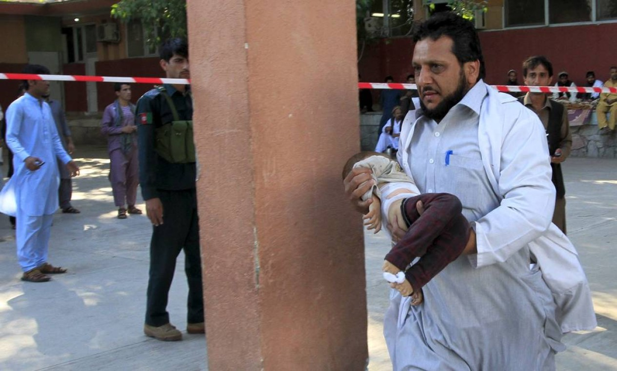 Voluntário corre com criança atingida no colo em um hospital em Jalalabad. As pessoas não sabiam para onde correr com o chão se movendo sob os pés Foto: PARWIZ / REUTERS