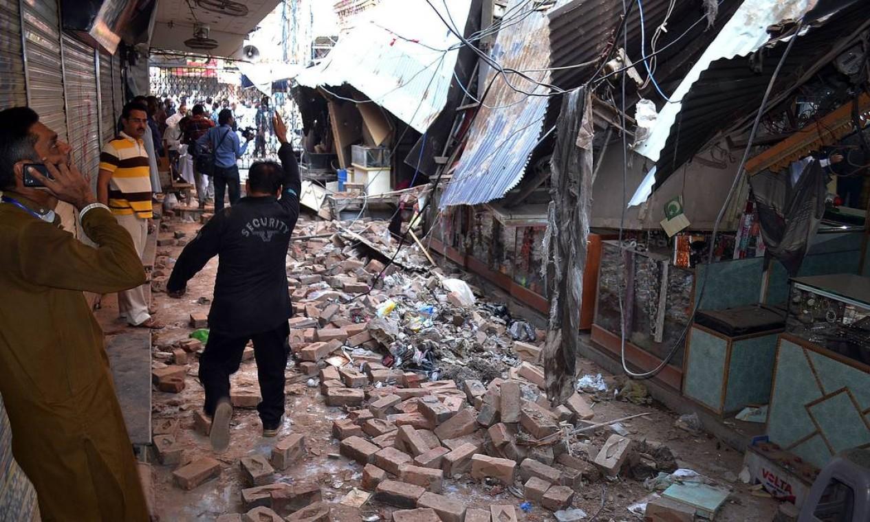 Paquistaneses atravessam escombros de mercado destruído em Sargodha Foto: SHAHID BUKHARI / AFP