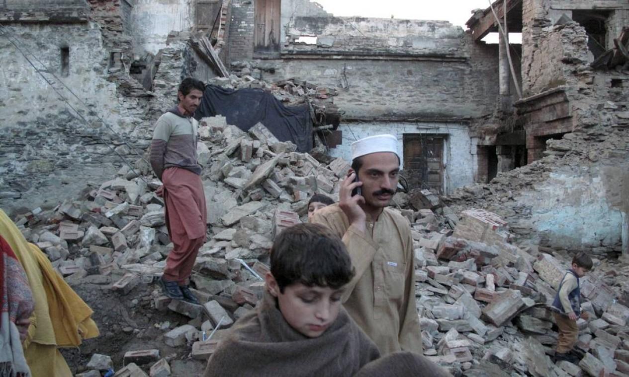 Sobre os escombros da casa destruída, paquistaneses tentam estabelecer contato. Em muitos pontos do sul do continente, os meios de comunicação ainda não foram reativados. Número de vítimas tende a crescer Foto: HAZRAT ALI BACHA / REUTERS