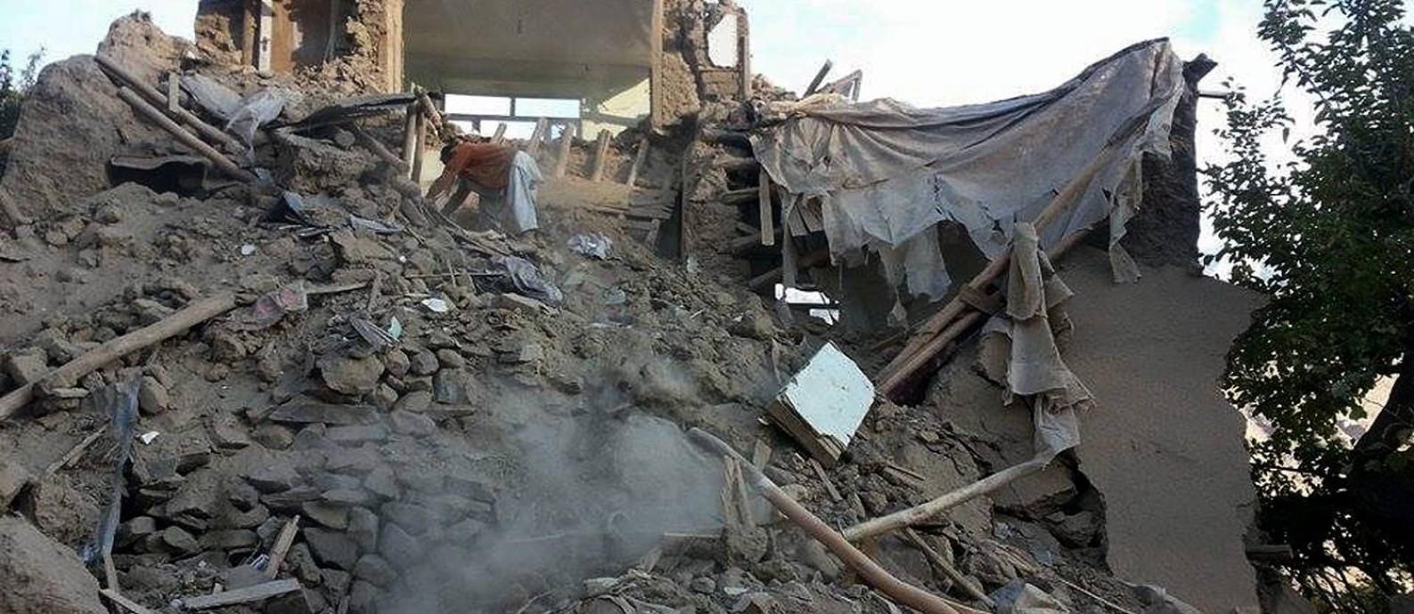 Afegão faz busca em meio aos destroços de um prédio em Ramankheel, no vale Panjshir, no Afeganistão, após terremoto de magnitude 7,5 Foto: STR / AFP
