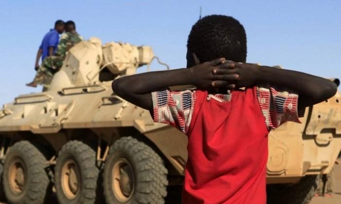 Em Darfur, garoto observa o tanque militar do governo se aproximando Foto: Reuters