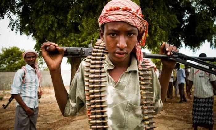 Jovem soldado ostenta munição e rifle Foto: AP
