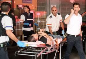 Homem ferido é socorrido após ataque em estabelecimento religioso em Tel Aviv. Cinco pessoas morreram em dois ataques distintos em Israel e na Cisjordânia Foto: MOSHE MIZRACHI / AFP