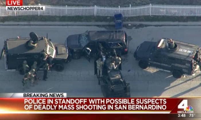 Veículos policiais cercam carro de suspeitos nas redondezas do local onde houve tiroteio Foto: AP