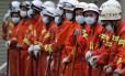 Trabalhadores chineses se preparam para começar os resgates. As autoridades culpam uma enorme montanha de terra procedente de obras de construção pelo deslizamento, que teria ocorrido depois de fortes chuvas