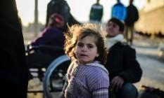 Menina faz parte de multidão bloqueada na fronteira da Síria com a Turquia Foto: BULENT KILIC / AFP