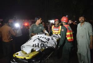Equipes de resgate retiram corpo da área Foto: ARIF ALI / AFP
