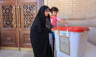 Menina deposita o voto da mãe em Shiraz, Irã, nas eleições desta sexta-feira Foto: HANDOUT / REUTERS