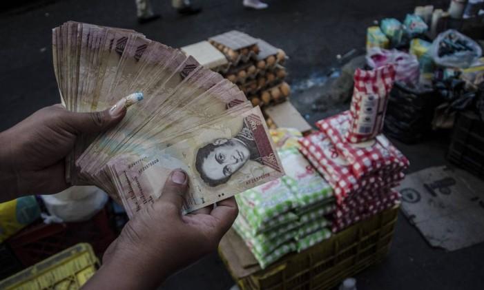 Trabalhadora do mercado negro mostra o dinheiro ganho em um dia nos arredores de Caracas. Eles passam horas na fila de supermercados para comprar produtos baratos e, depois, os revendem na rua Foto: MERIDITH KOHUT / NYT