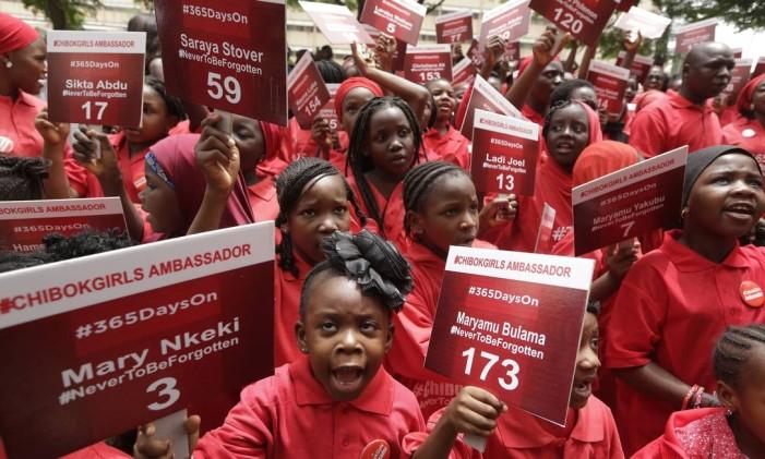 """Jovens conhecidas como """"embaixadoras de Chibok"""" carregam placas com os nomes das desaparecdas em manifestção na Nigéria Foto: Sunday Alamba / AP"""