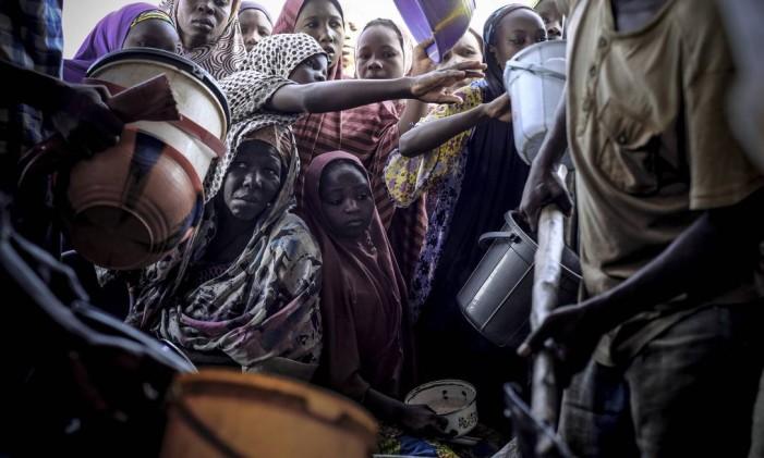 Nigerianas que fugiram do Boko Haram recebem alimentos em programa da ONU e da Cruz Vermelha para civis que escaparam do grupo terrorista Foto: ASHLEY GILBERTSON / NYT