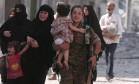 Combatente das Forças Democráticas Sírias ajudam famílias em libertação da cidade de Manbij do controle do Estado Islâmico Foto: RODI SAID / REUTERS