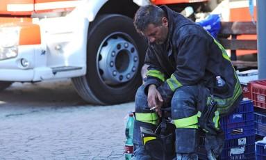 Após quase 24h de trabalho sem descanso, bombeiro pausa para repouso em Amatrice Foto: MARCO ZEPPETELLA / AFP