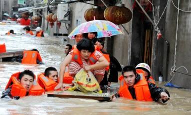 Bombeiros ajudam no resgate de vítimas do tufão, no leste da China. Foto: STR / AFP