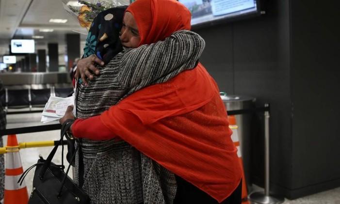 Mãe e filha somali se abraçam ao se reencontrarem, após uma corte americana suspender a ordem executiva de Trump que havia impedido a entrada da filha nos EUA. Foto: WIN MCNAMEE / AFP