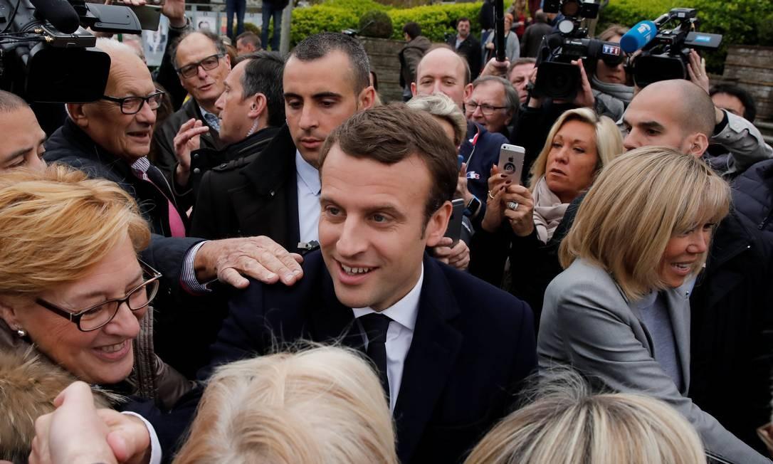 O ex-ministro da Economia chegou ao posto de votação acompanhado da esposa, Brigitte Trogneux, e foi cercado por apoiadores Foto: BENOIT TESSIER / SAA/