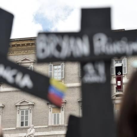 Venezuelanos segurando cruzes com nomes de vítimas da repressão aos protestos contra o governo no país fazem manifestação na Praça de São Pedro enquanto o Papa Fracisco, na janela ao fundo, se prepara para entoar o cântico Regina Coeli Foto: TIZIANA FABI / AFP