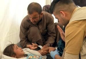 Homem conforta criança enquanto médico dá assistência após suspeita de envenenamento alimentar Foto: Balint Szlanko / AP