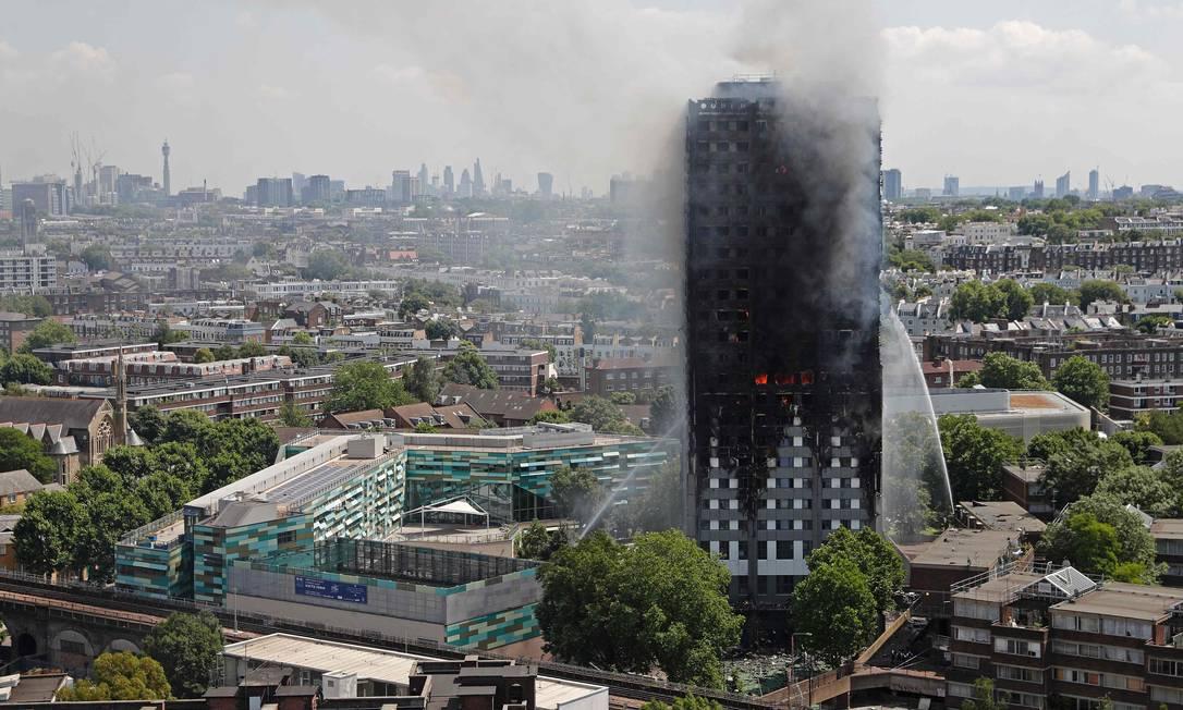 Em ângulo aberto, é possível ver as duchas d'água que os bombeiros dispararam contra o fogo no arranha-céus de 24 andares Adrian Dennis / AFP