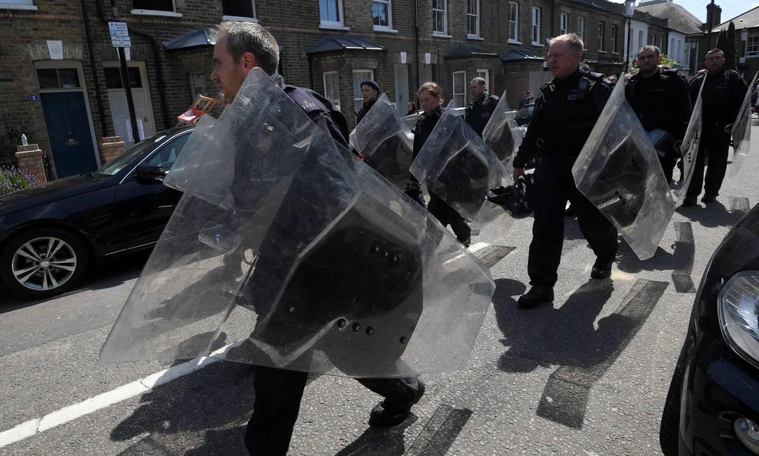 Agentes de polícia chegam com forte equipamento de segurança para enfrentar o fogo na Grengell Tower TOBY MELVILLE / REUTERS