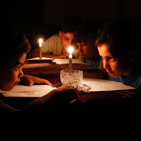 Crianças palestinas leem à luz de velas. Diante de pagamento menor, Israel reduz fornecimento de energia à Faixa de Gaza Foto: THOMAS COEX / AFP / 13/06/2017
