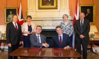 A primeira-ministra britânica Theresa May (dir.) junto à líder do DUP, Arlene Foster (esq.) com representantes dos partidos na assinatura de coalizão Foto: Daniel Leal-Olivas / REUTERS