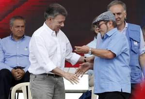 O presidente da Colômbia, Juan Manuel Santos, e o líder das Farc, Rodrigo Londoño, se cumprimentam na cerimônia que marca a conclusão da entrega das armas da guerrilha Foto: Fernando Vergara / AP