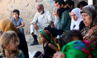 Grupo de sírios que fugiu de áreas sob controle do EI em Raqa se reúne no subúrbio de Jazra, em Raqa Foto: Delil Souleliman / AFP