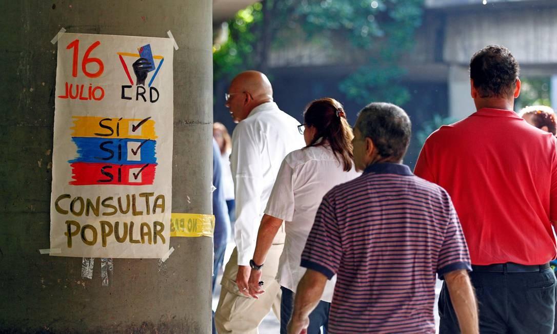 Cartaz próximo a um ponto de votação em Caracas durante a consulta opositora sobre o plano do governo do presidente da Venezuela, Nicolás Maduro, de reformular a Constituição Foto: CHRISTIAN VERON / REUTERS