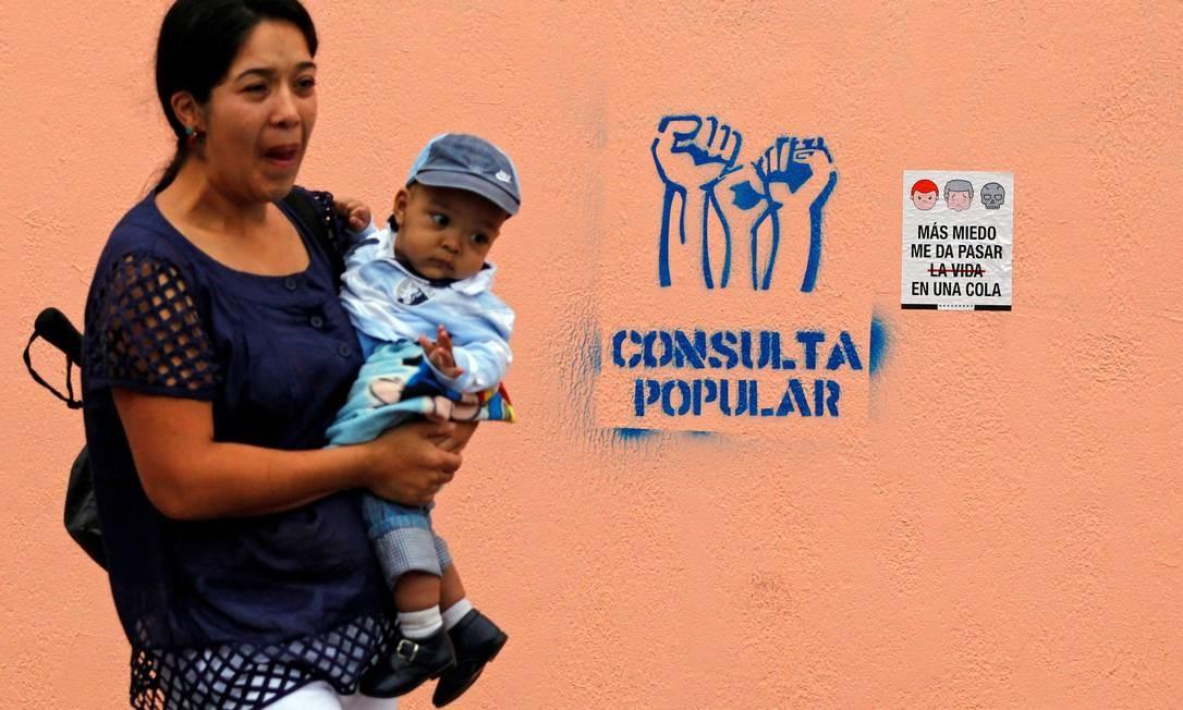 """No dia da consulta popular organizada pela oposição na Venezuela sobre o governo Nicolás Madro, mulher passa com bebê no colo por anúncios sobre o referendo em Caracas. Um deles diz: """"Tenho mais medo de passar a vida em uma fila"""" Foto: CHRISTIAN VERON / REUTERS"""