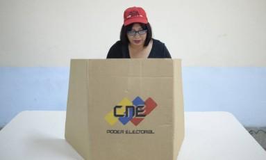 Cidadã venezuelana vota em apoio ao presidente Nicolás Maduro em Caracas, na simulação da eleição da nova Constituinte (que será em 30 de julho), convocada pelo governo para este sábado (16/7), no mesmo dia em que a oposição realizou consulta popular contra os planos do governo de mudar a Constituição do país Foto: FEDERICO PARRA / AFP