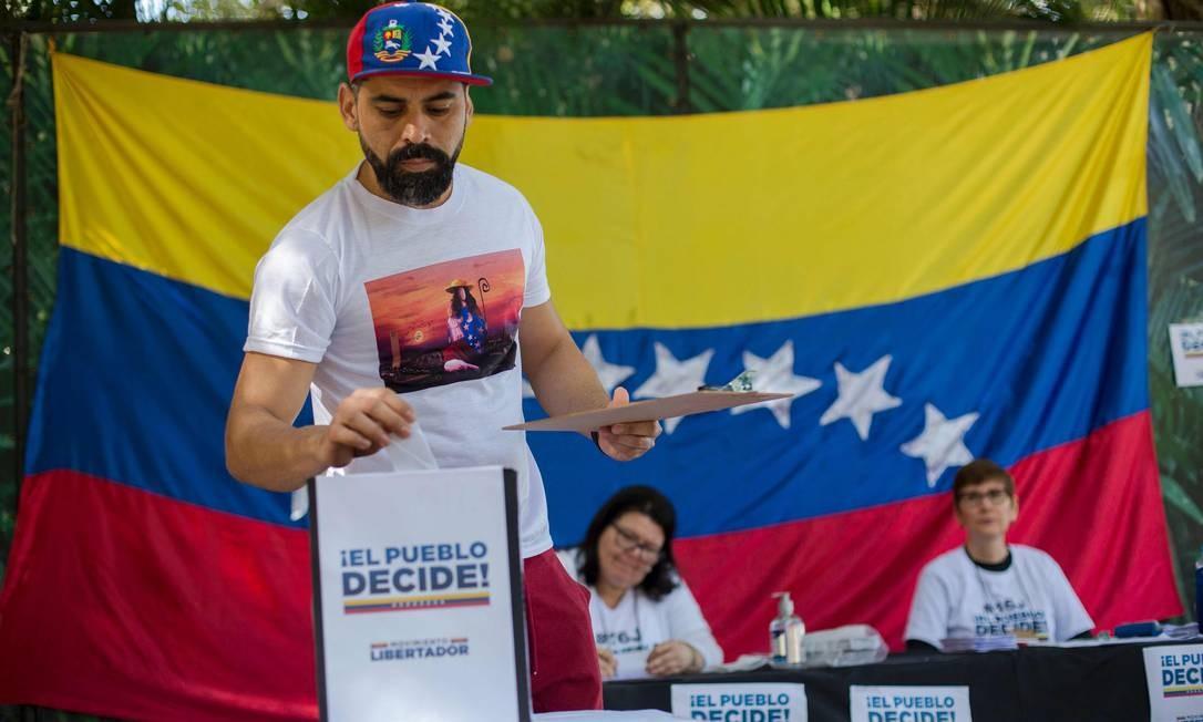 Venezuelanos residentes no Brasil também participaram da consulta opositora sobre o projeto de reformular a Constituição da Venezuela. Na foto, cidadão venezuelano deposita seu voto no Rio de Janeiro Foto: MAURO PIMENTEL / AFP