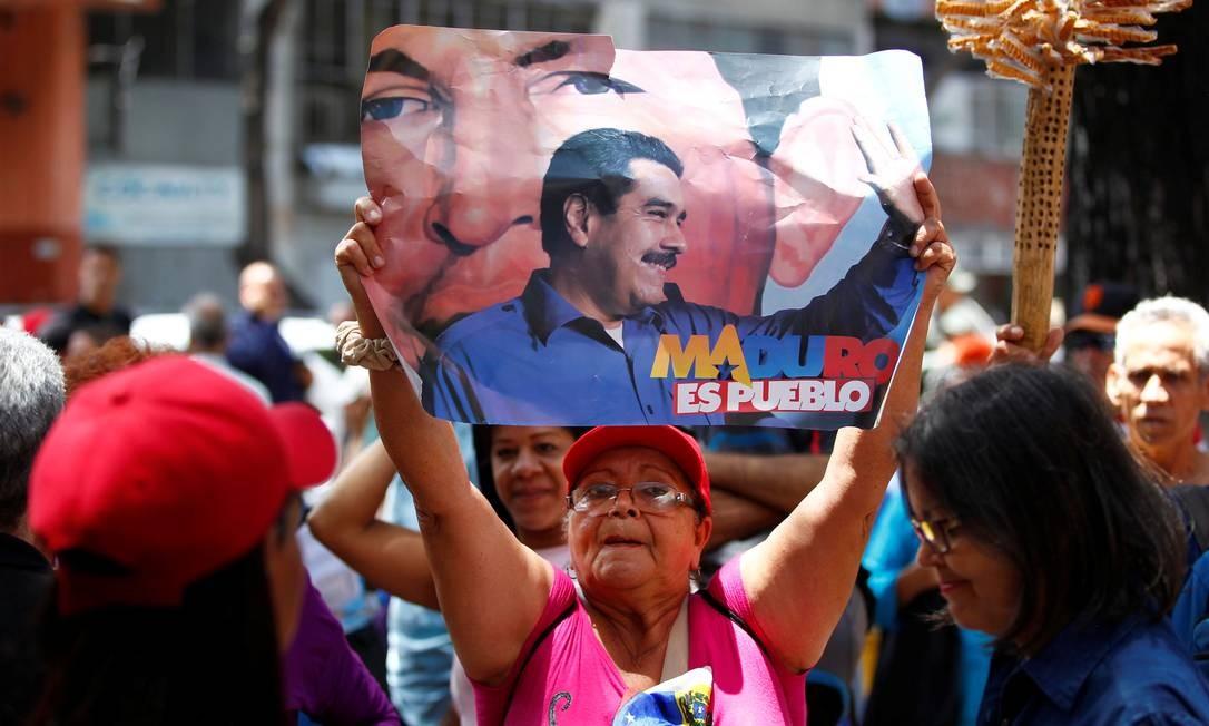 Mulher manifesta apoio ao governo venezuelano, segurando um cartaz com a foto do presidente Nicolás Maduro e Hugo Chávez, durante a simulação da eleição da nova Constituinte, convocada pelo governo no mesmo dia da consulta popular da oposição sobre os planos de Maduro de reescrever a Constituição Foto: CHRISTIAN VERON / REUTERS