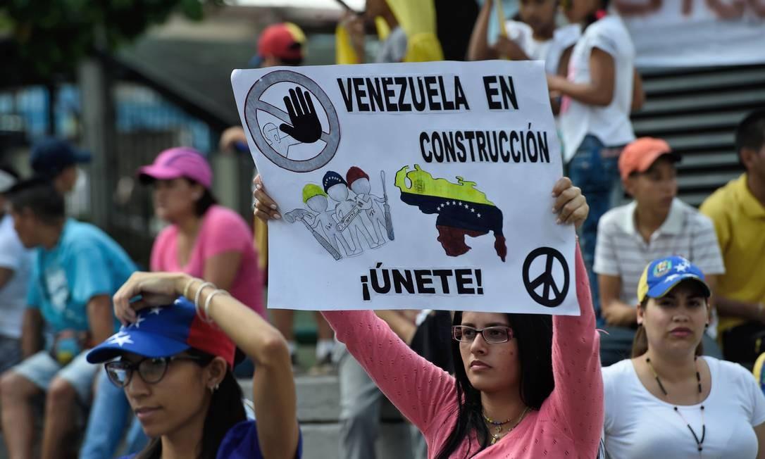 No cartaz levado pela manifestante em Caracas, a mensagem é anti-governista Foto: JUAN BARRETO / AFP