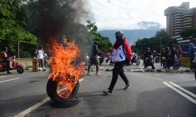 Manifestantes bloqueiam avenida durante protesto antigoverno em Caracas como parte de ato da greve geral de 24 horas convocada pela oposição Foto: RONALDO SCHEMIDT / AFP