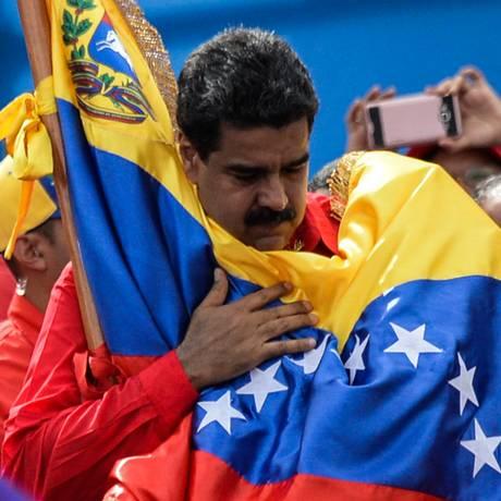 O presidente da Venezuela, Nicolás Maduro, abraça a bandeira do país Foto: FEDERICO PARRA / AFP
