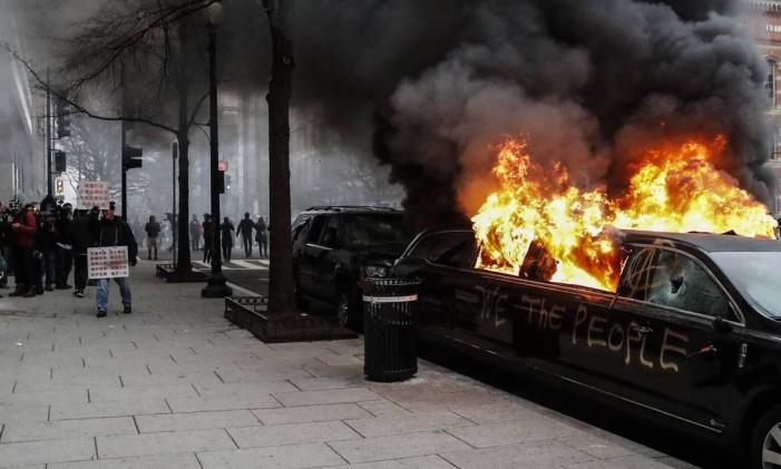 Uma limusine é incendiada druante manifestação após a cerimônia de posse do presidente Donald Trump, em 20/1/2017, no centro de Washington Foto: John Minchillo / AP/20-1-2017