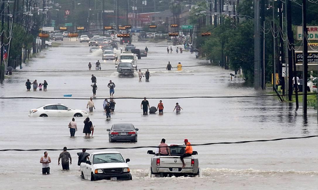 Cidadãos caminham em meio à inundação no centro de Houston Foto: THOMAS B. SHEA / AFP