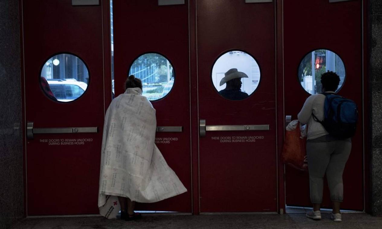 Mulher olha pela janela de abrigo instalado em centro de convenção em Houston Foto: BRENDAN SMIALOWSKI / AFP