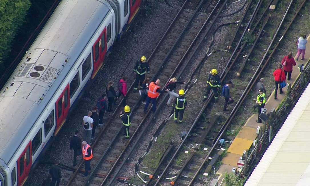 Agentes de emergência ajudam pessoas a desembarcar de trem próximo à estação Parsons Green AP