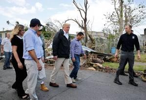 O presidente Donald Trump caminha entre os destroços nas ruas de Guaynabo, em Porto Rico, com a primeira-dama Melania Trump Foto: Jonathan Ernst / Reuters