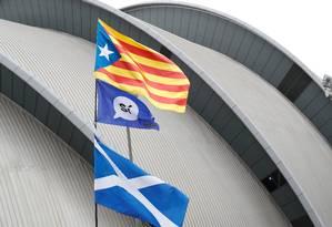 Bandeiras da Escócia e da Catalunha erguidas durante a conferência do Partido Nacional Escocês em Glasgow Foto: RUSSELL CHEYNE / REUTERS