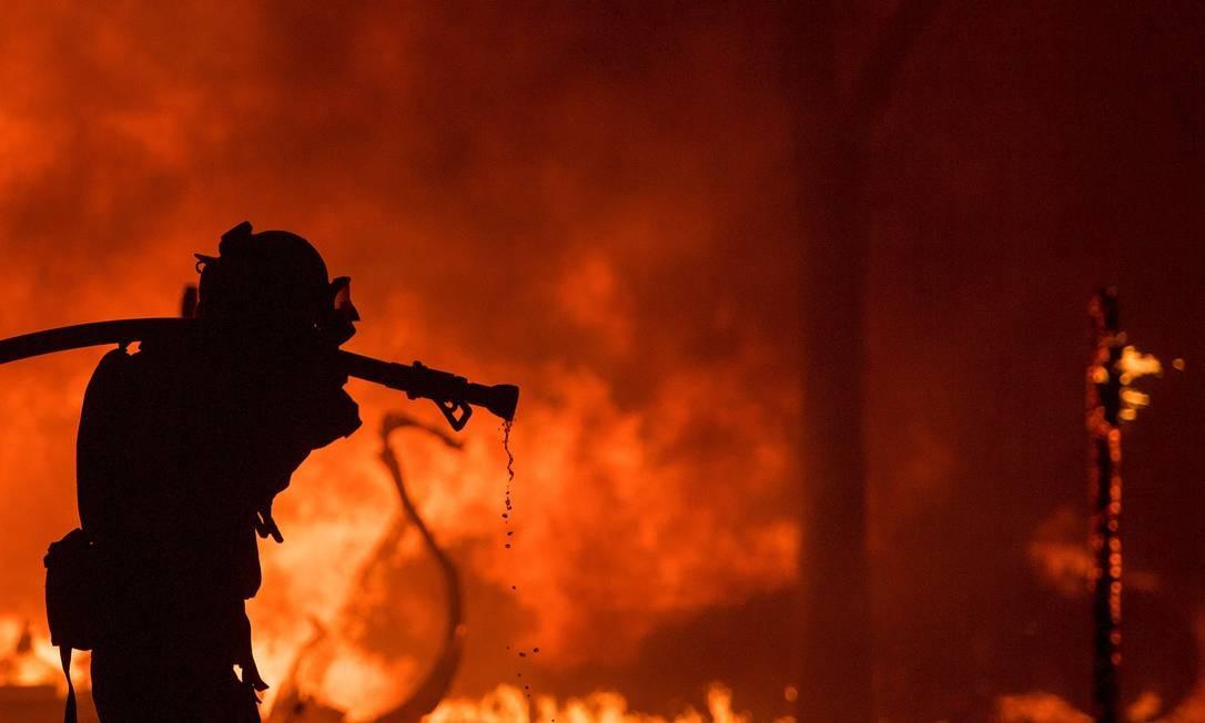 Bombeiro carrega mangueira em frente a uma casa da região de Napa, na Califórnia JOSH EDELSON / AFP