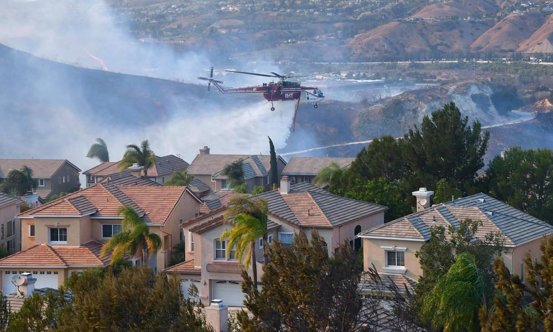 Helicóptero despeja água sobre casas do bairro de Anaheim Hills, em Anaheim FREDERIC J. BROWN / AFP